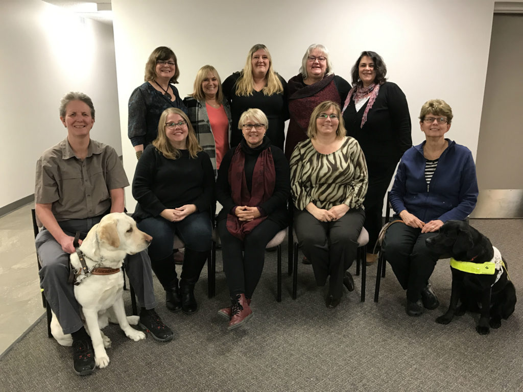 Group photo of board members - Back row: Sherry Grabowski (CNIB), Laurie Marrissen (Lions McInnes House), Jennifer Robbins (CHKC), Roxanna Spruyt-Rocks (DeafBlind Ontario Services), Karen Chambers (Bob Rumball Centre of Excellence for the Deaf) First row: Megan McHugh (CNSDB), Marta Zaharia (IOO), Cathy Proll (CDBA), Lynne Osasuyi (WRMS), Kim Wrigley-Archer (member-at-large)